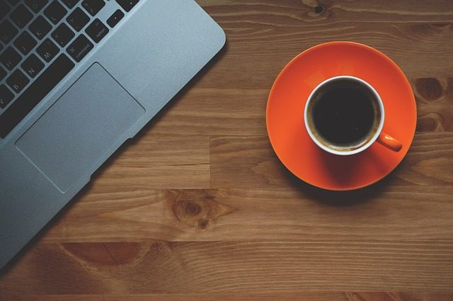 Un MacBook à côté d'une tasse de café
