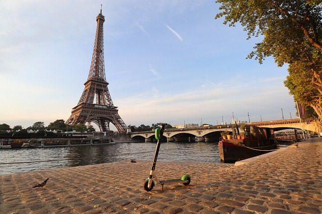 Une trottinette posant devant la Tour Eiffel à Paris