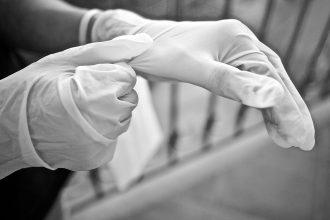 Un homme enfilant des gants en plastique