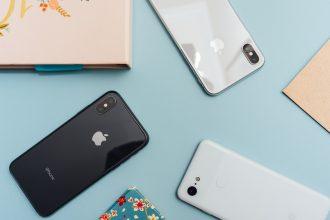 Des iPhone posés sur un bureau, aux côtés d'un Pixel 3