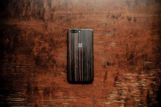 Un OnePlus posé sur une table en bois, face contre le sol