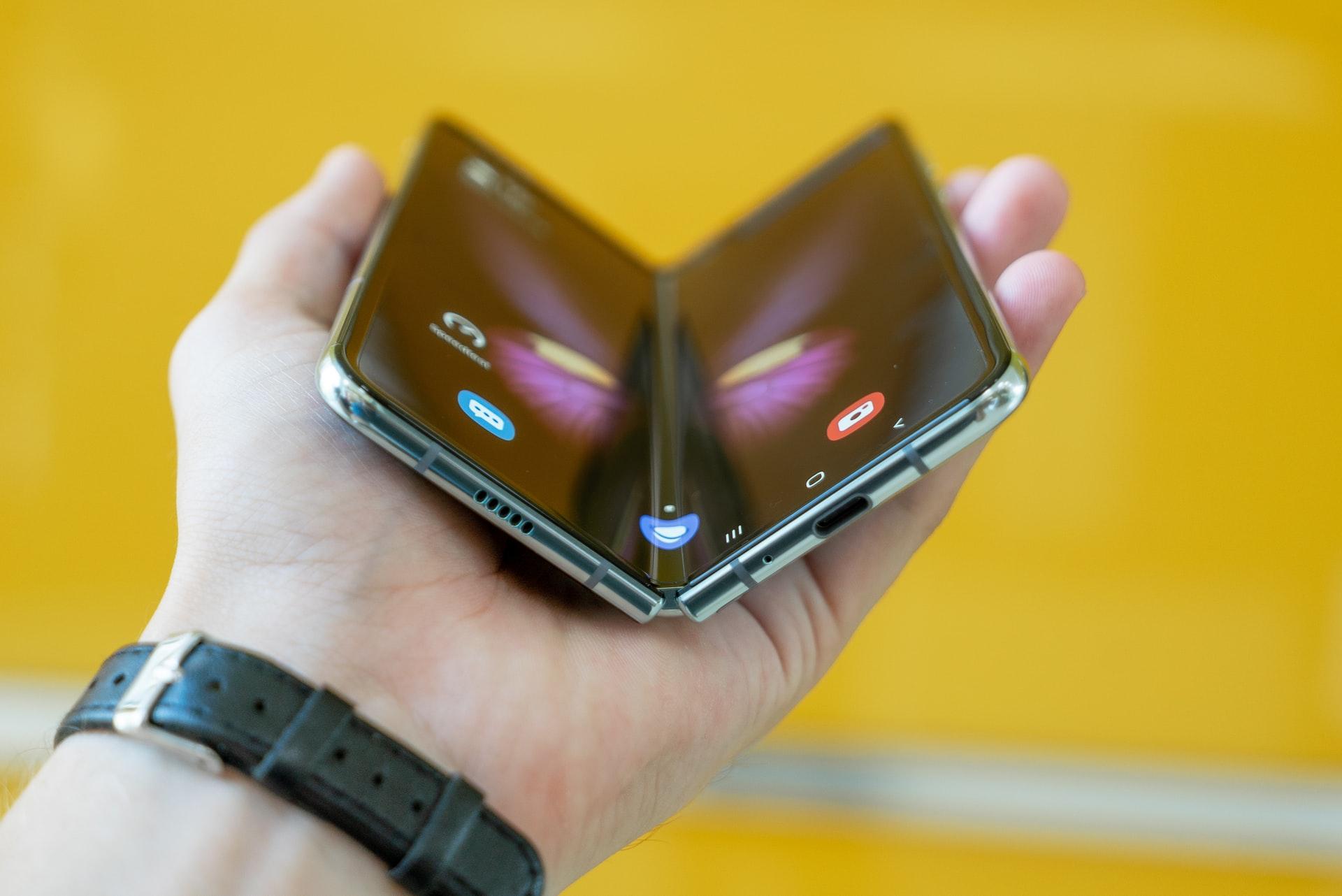 Un Galaxy Fold tenu en main, à moitié plié