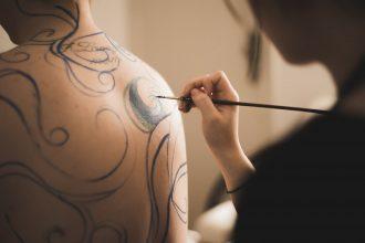 Une artiste peignant le corps d'une femme