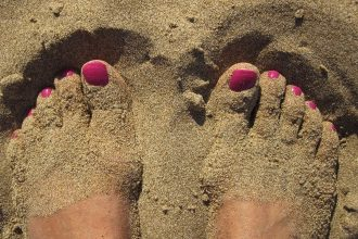 Une femme les pieds dans le sable