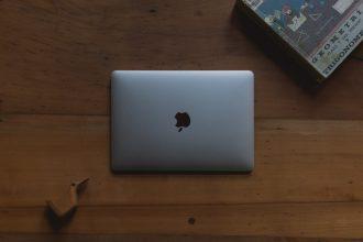Un MacBook posé sur une table en bois