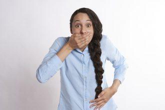 Une jeune femme riant en se cachant la bouche
