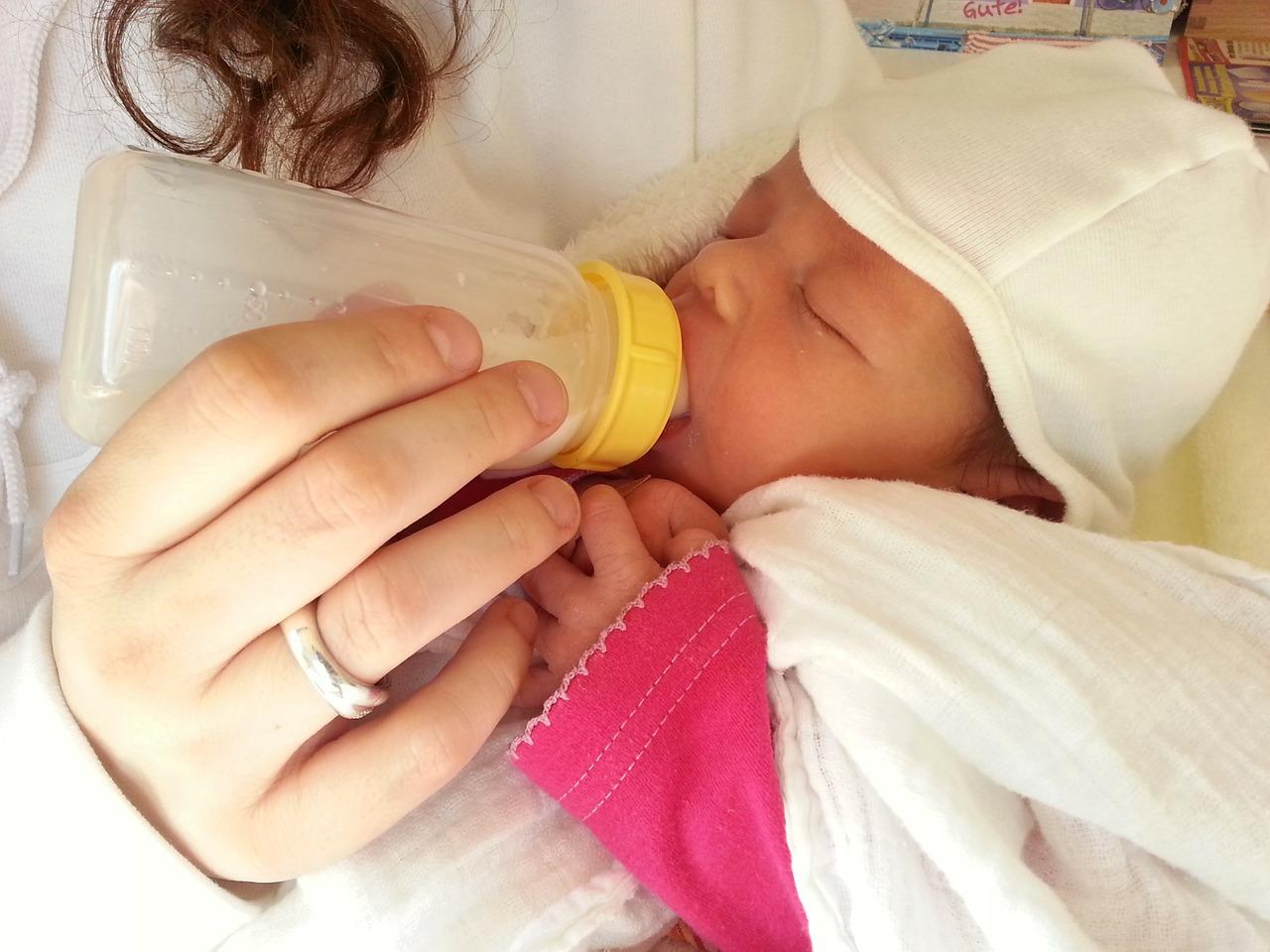 Photo d'un bébé alimenté avec un biberon