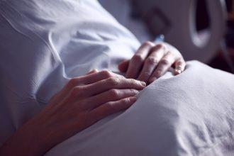 Les mains d'un patient reposant sur un oreiller