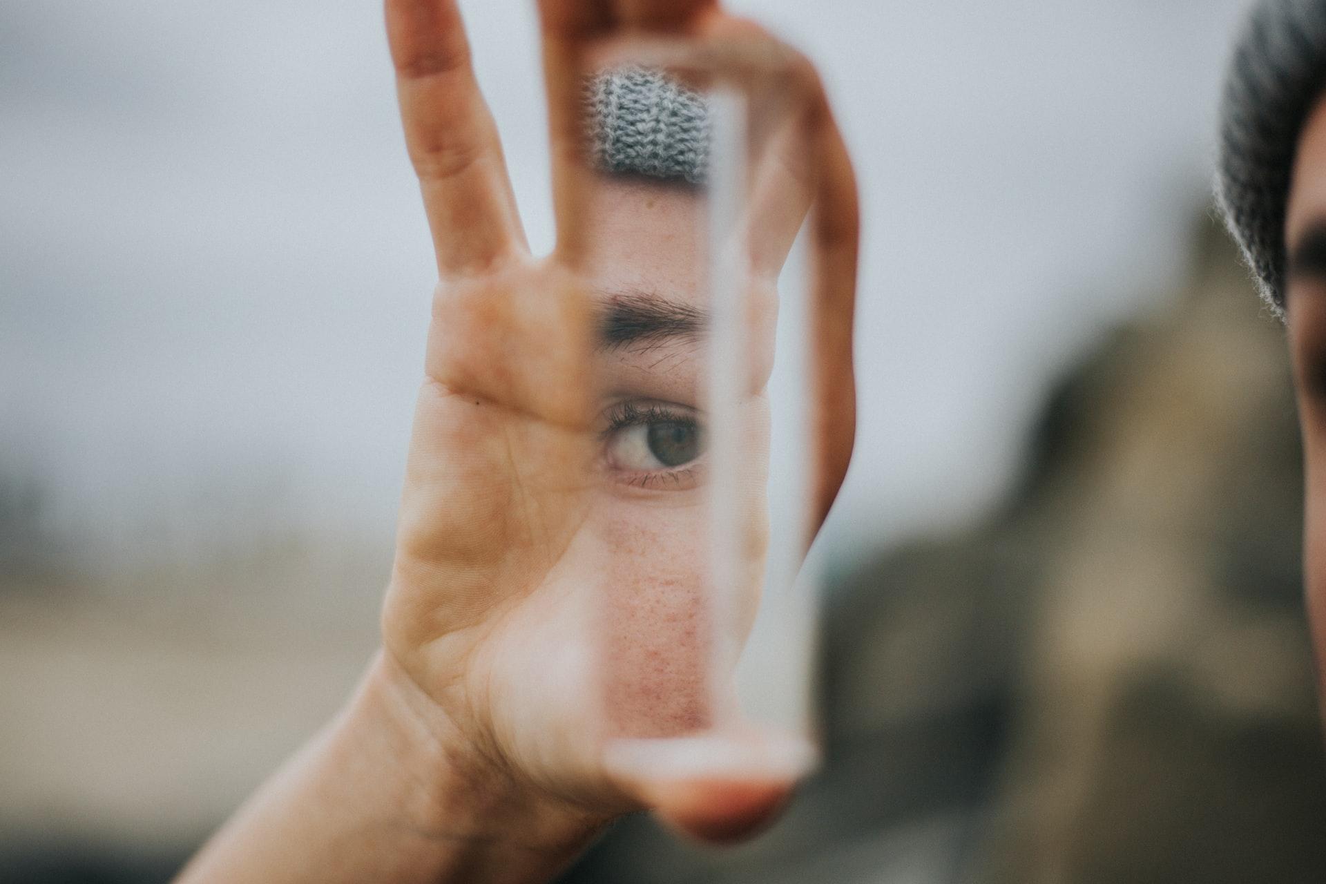 Une femme tenant l'éclat d'un miroir