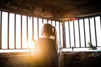 Une jeune femme attendant la fin du confinement devant sa fenêtre