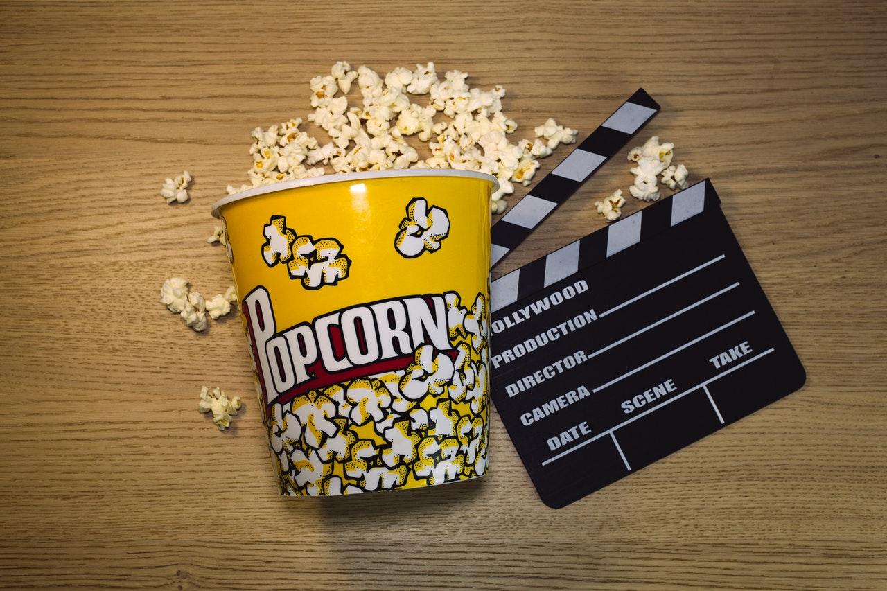 Un pot de popcorn à côté d'un clap de cinéma
