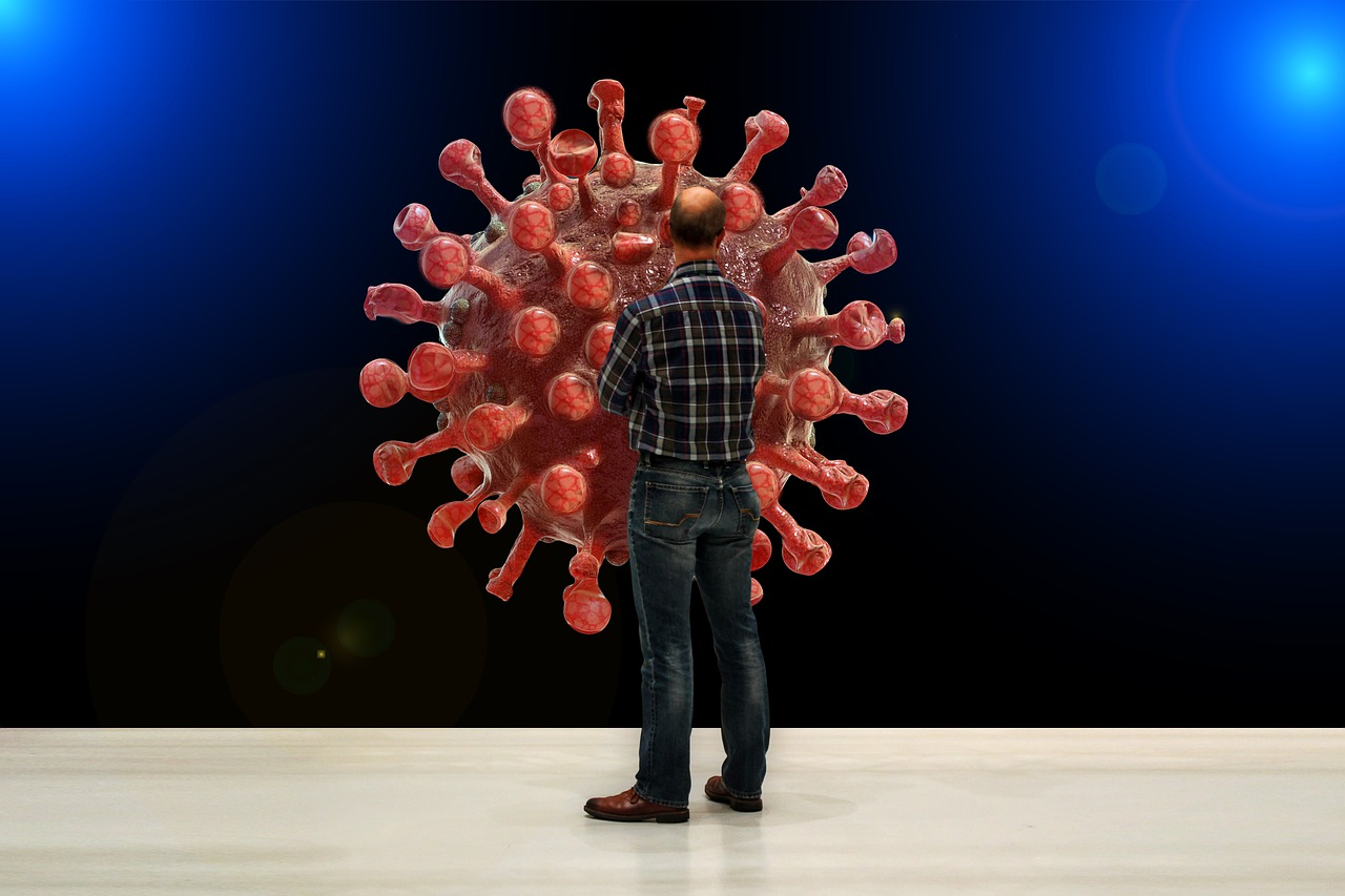 Un homme se tenant devant une sculpture ayant la forme d'un virus