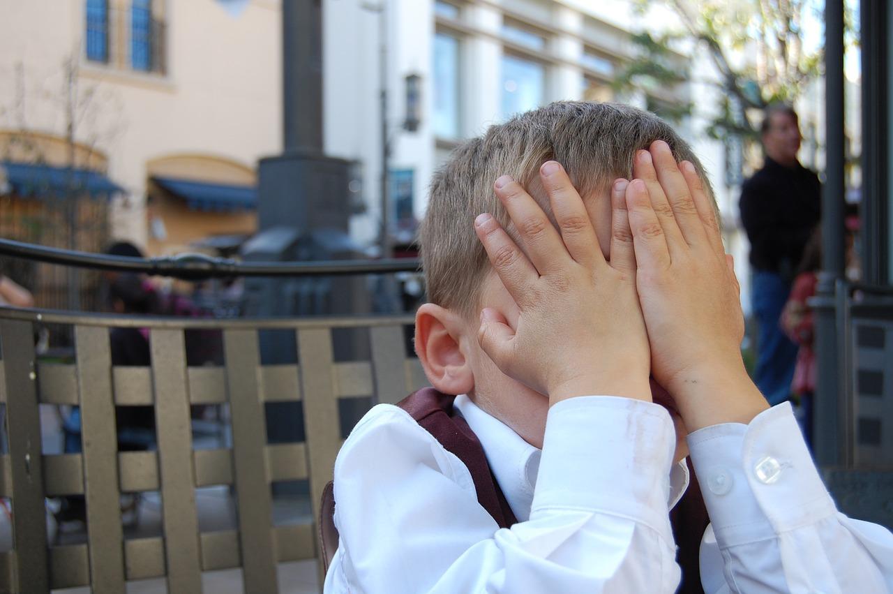 Un enfant se tenant le visage entre les mains