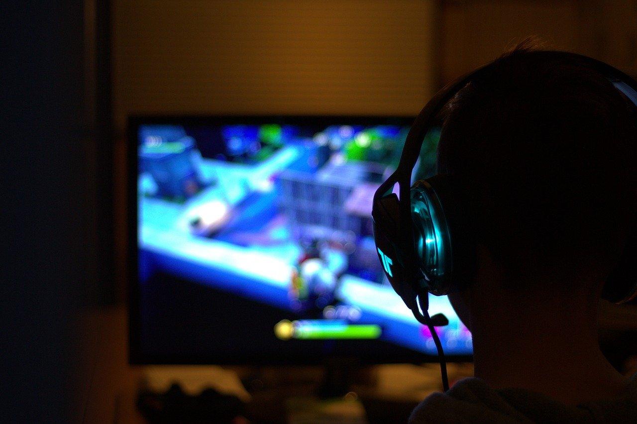 Un joueur devant son écran, un casque sur les oreilles