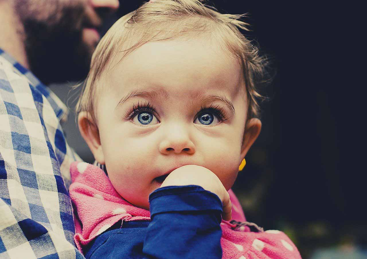 La photo d'un bébé tenu dans les bras d'un homme