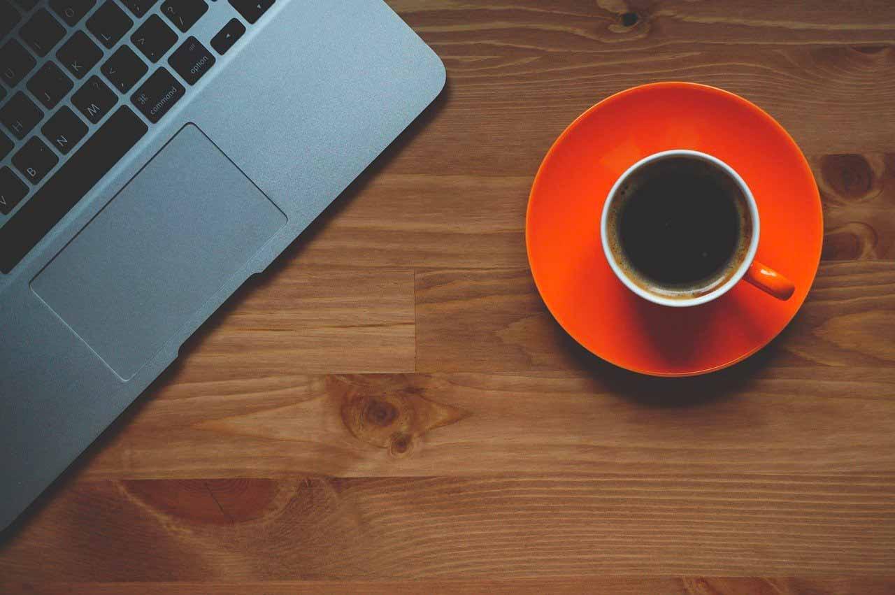 Une tasse de café à côté d'un ordinateur