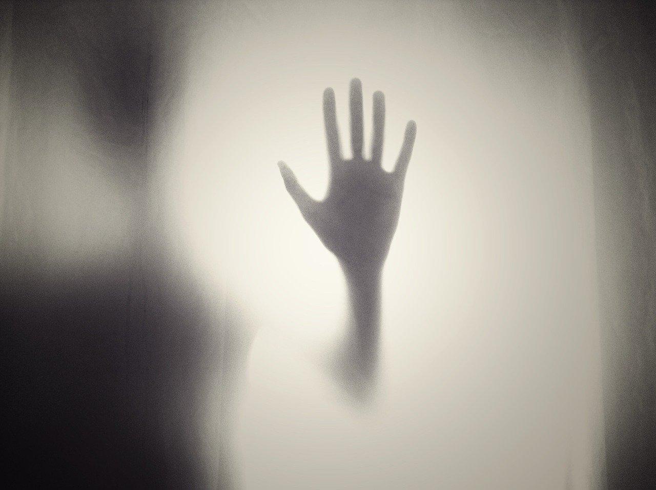 Une main derrière un drap