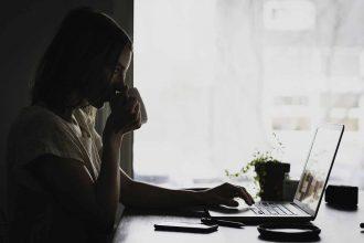 Une femme buvant un café devant l'écran d'un ordinateur