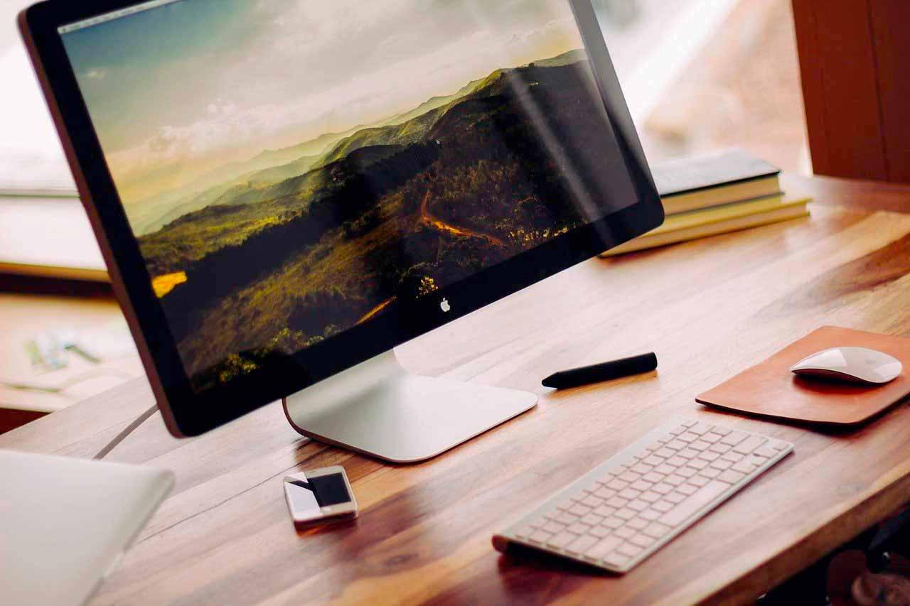 Un Apple Display sur un bureau en bois