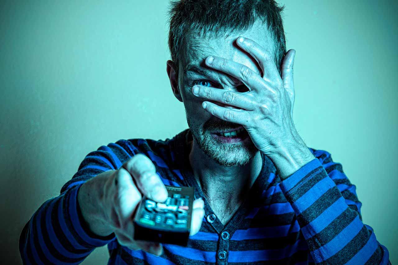 Un homme tenant une télécommande, la main sur son visage
