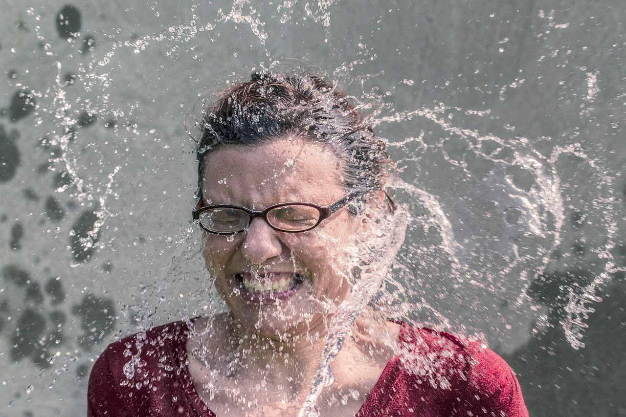 Une femme se prenant un seau d'eau