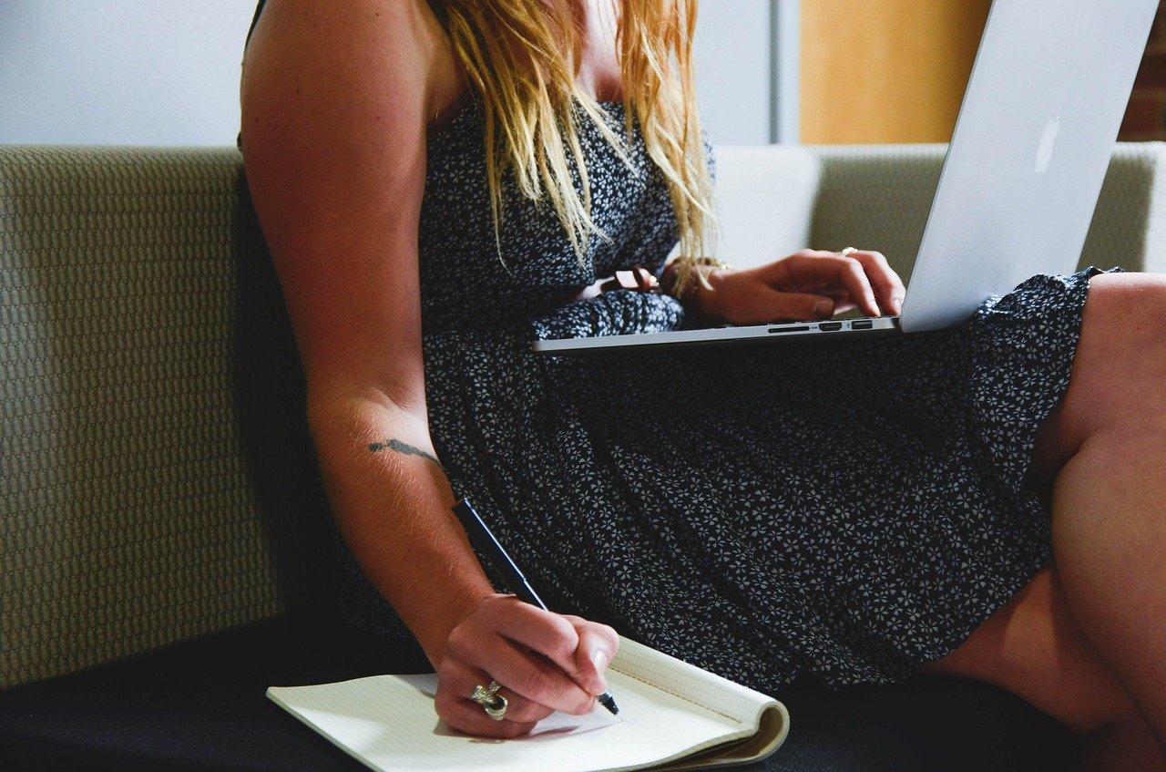 Une femme en train d'écrire quelque chose sur un cahier