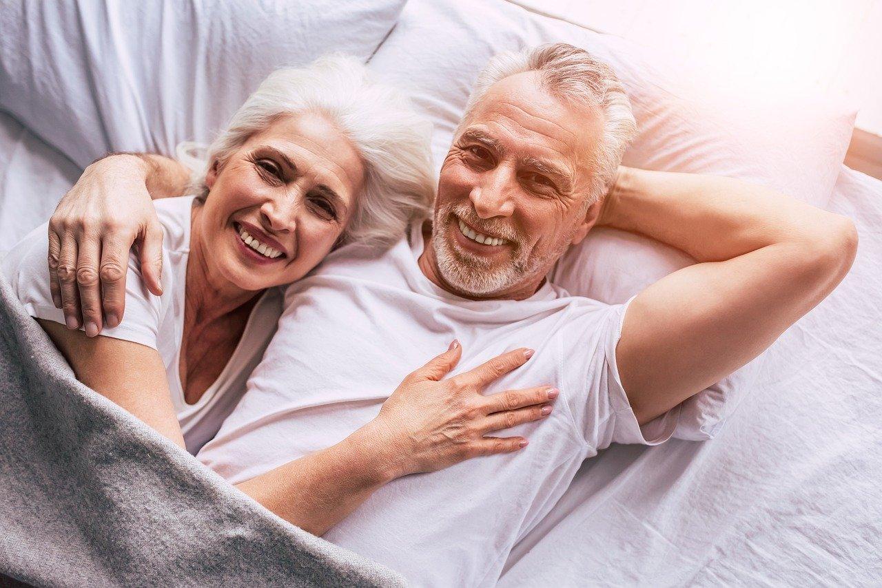 un couple âgé dans un lit, un sourire aux lèvres
