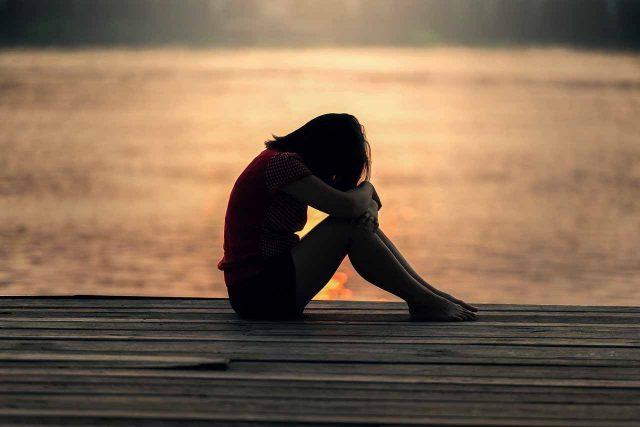 Une adolescente se tenant la tête dans ses mains