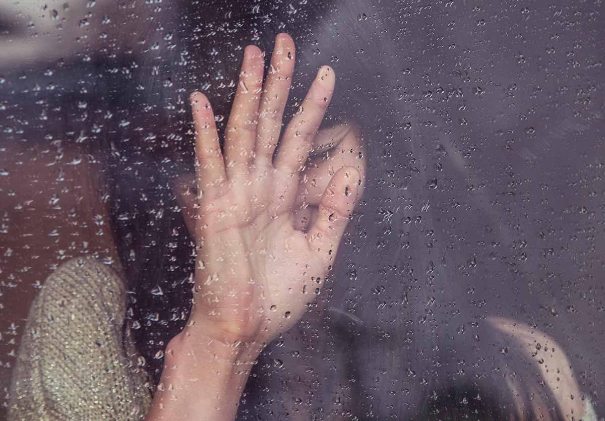 Une jeune fille la main posée sur une vitre