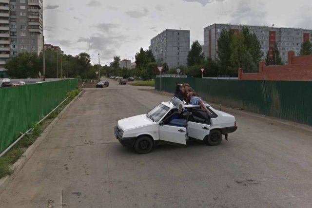 Un homme et une femme assis sur le toit de leur voiture