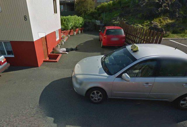Un homme endormi entre deux voitures
