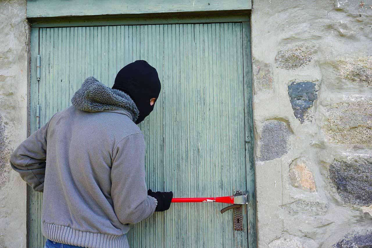 Une personne en train d'entrer par effraction dans une maison