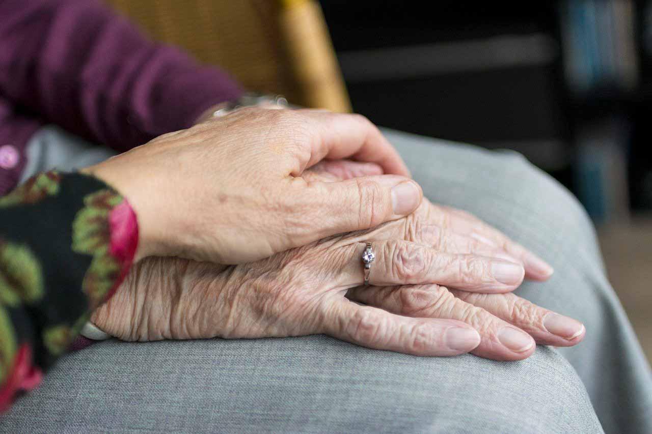 Deux personnes âgées se tenant la main