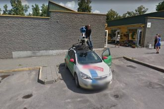 Un chauffeur de Google Car en train de s'afférer sur la caméra de son véhicule