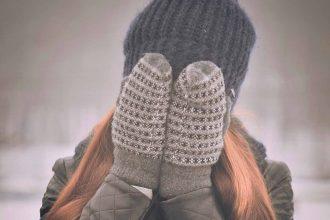 Une femme se tenant le visage dans les mains, avec un bonnet et des gants