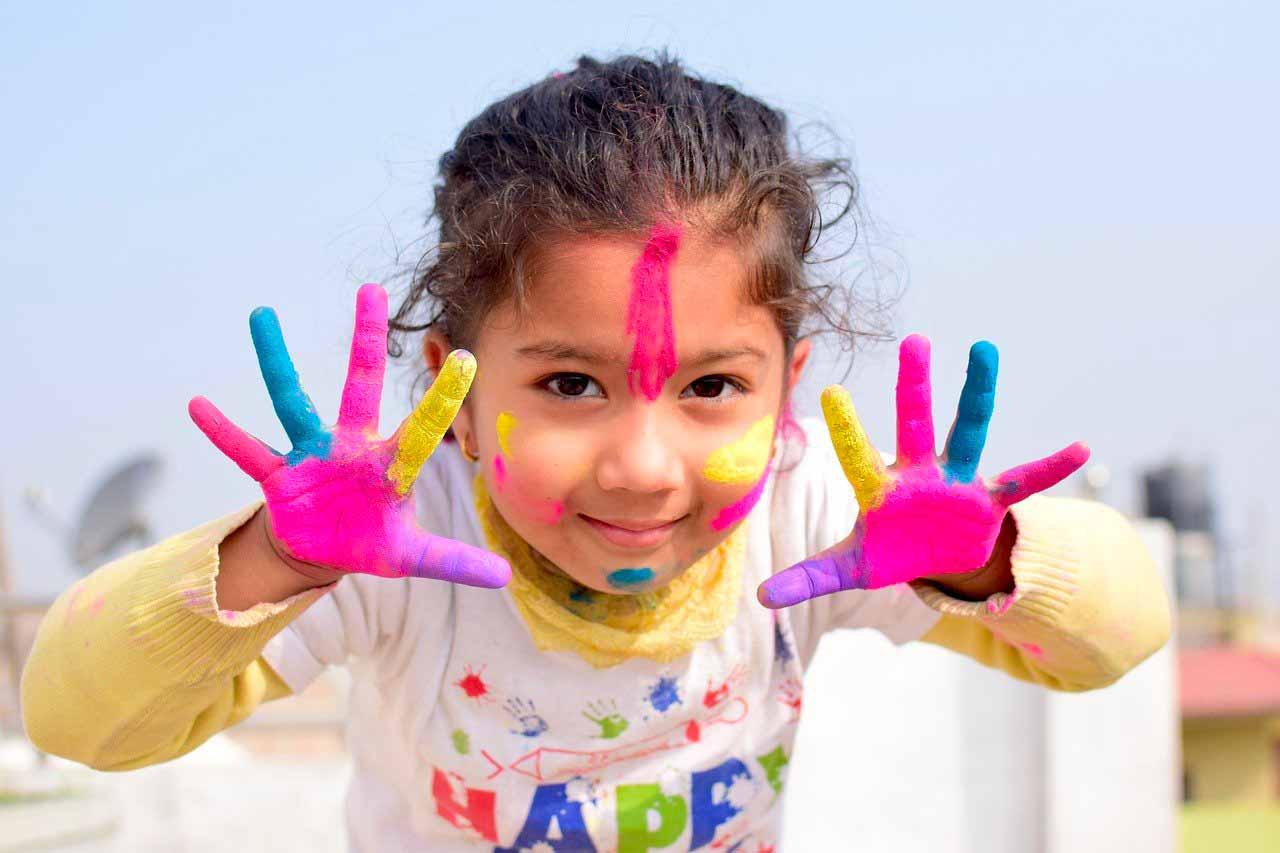 La photo d'une fillette, les mains pleine de peinture