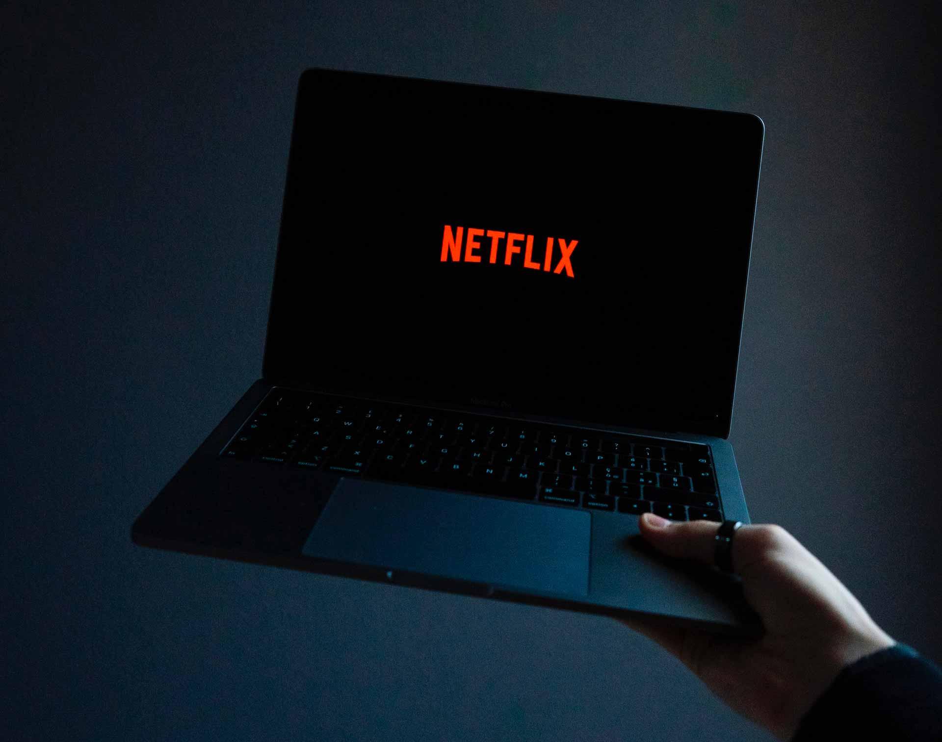 Netflix sur un ordinateur portable tenu à bras levé