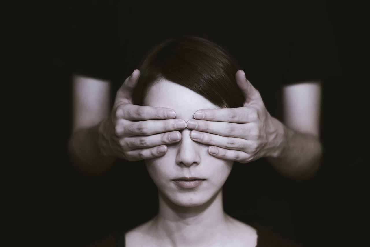 Une femme avec des mains posées sur ses yeux