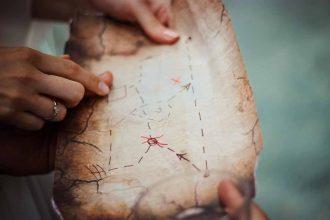 Une carte au trésor tenue en mains