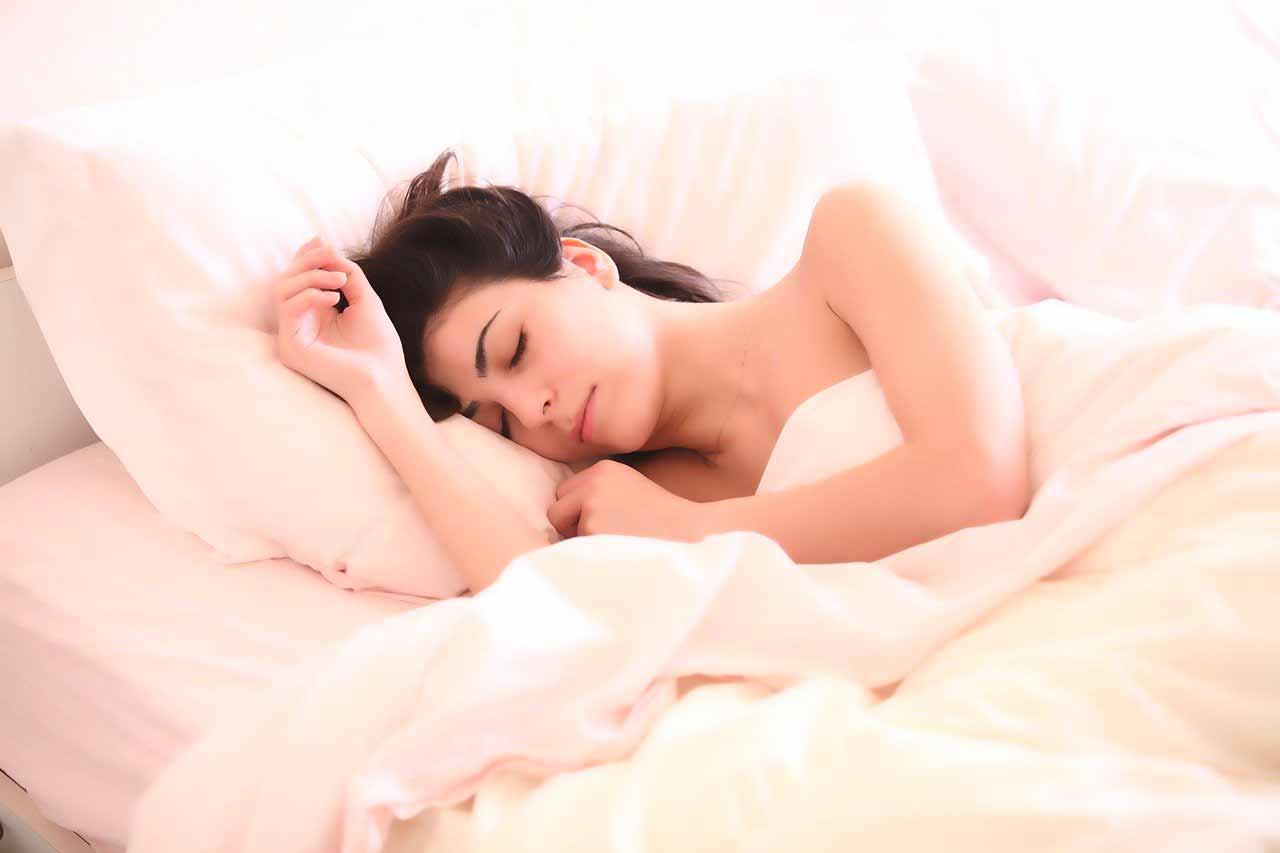 Une femme en train de dormir dans son lit