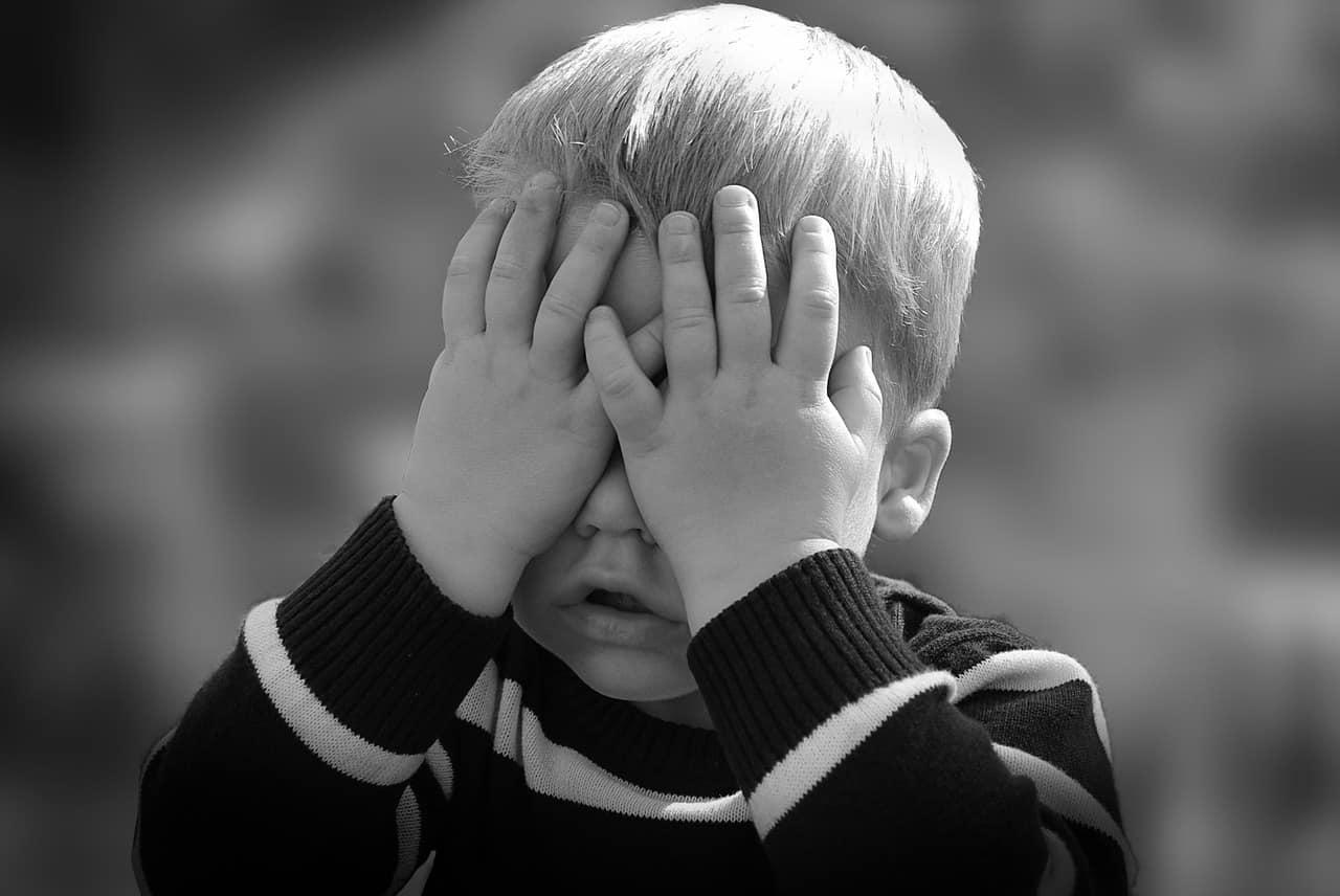 Un enfant se cachant le visage entre les mains